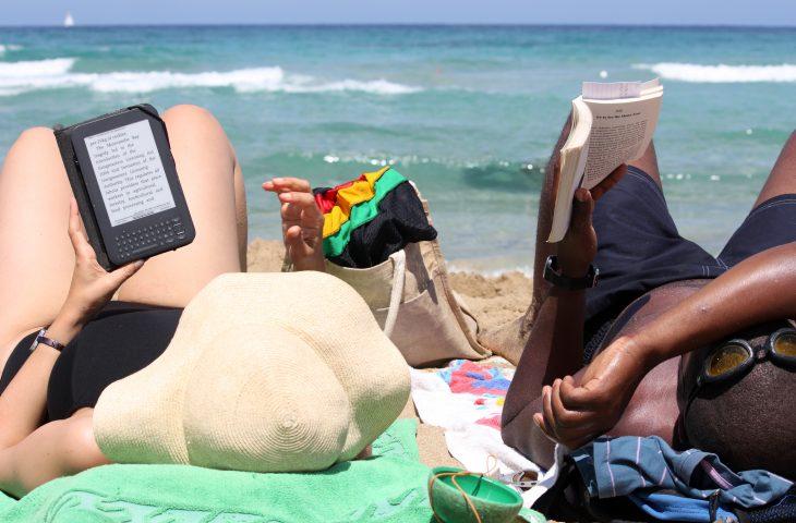 para leżąca na plaży czytająca książki
