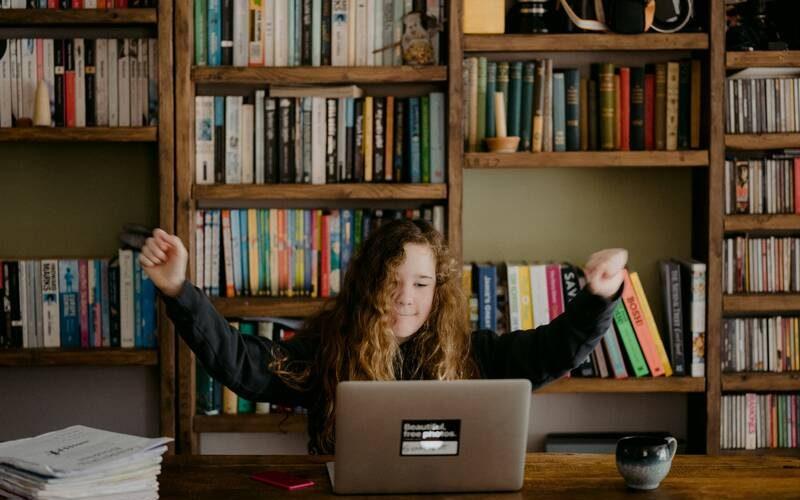 Dzieko w urządzony pokoju uczące się przy komputerze