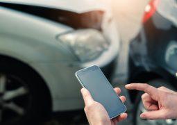 telefon komórkowy na tle uszkodzonego w wypadku samochodu